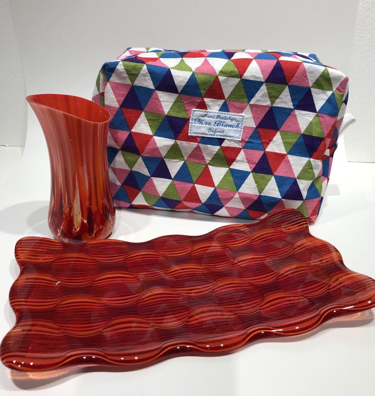 Red glass bud vase, multicoloured wash bag and red stripy glass dish