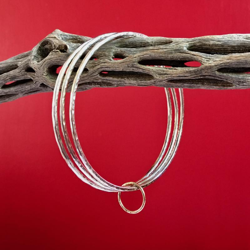 Three hammered silver bangles linked by a 9 carat gold ring.  Inner diameter 6.5cm (medium). £80