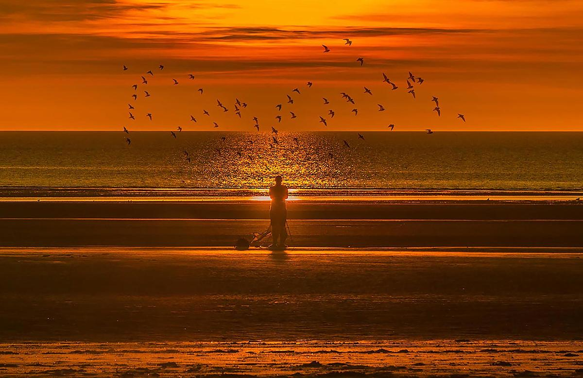Person alone on a beach with the sun setting