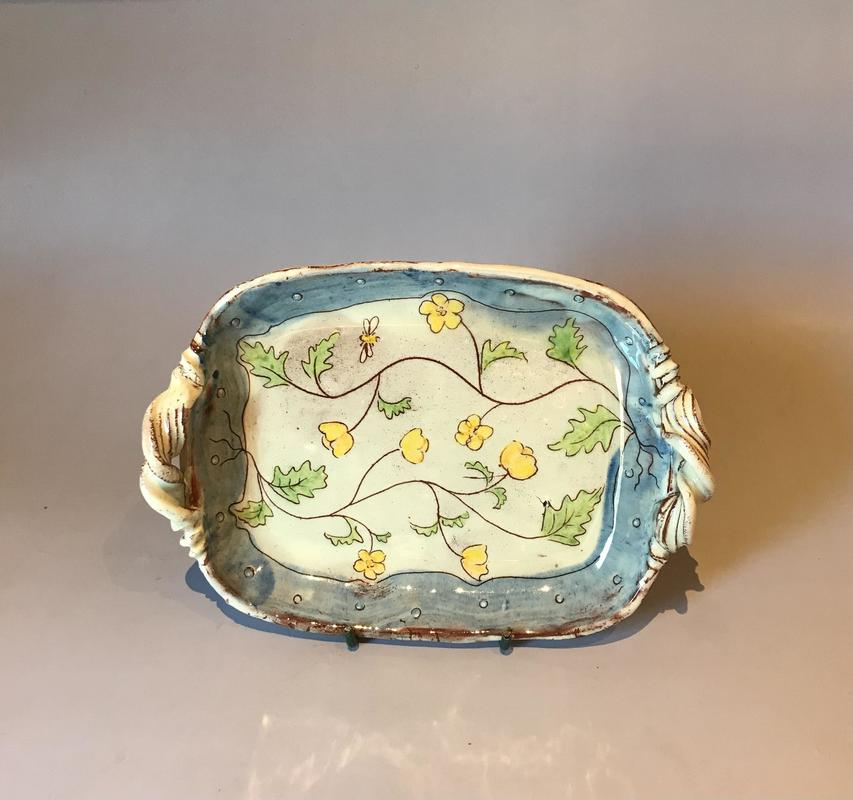 Slip ware dish with handles and sgraffito design.