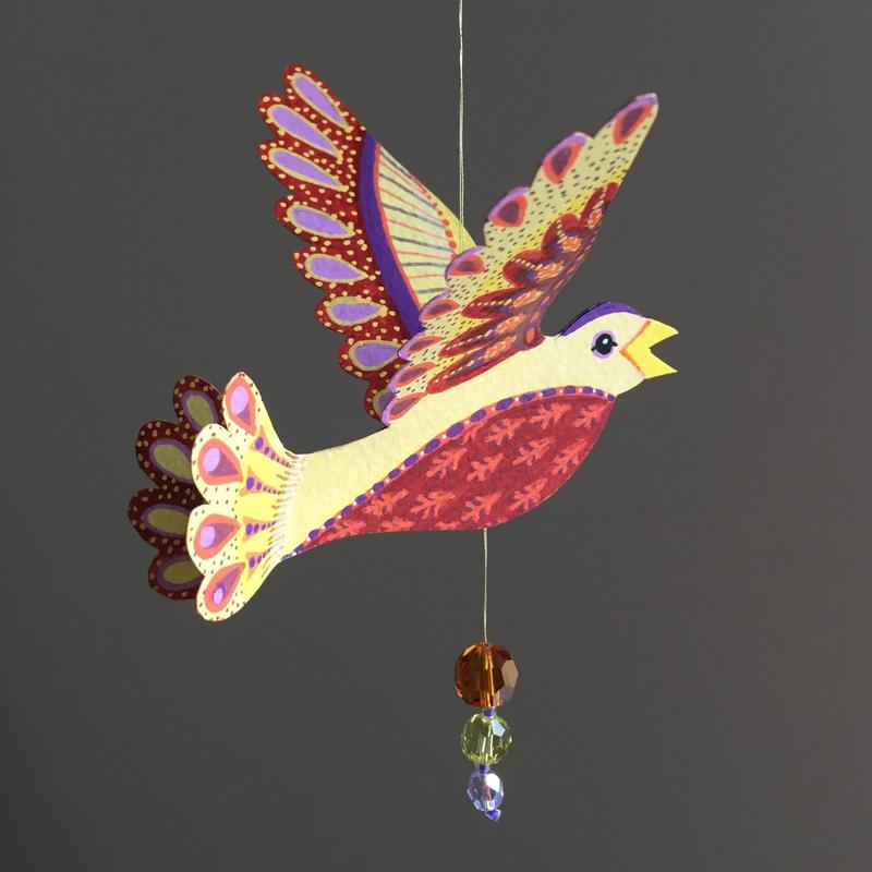 Yellow and Red tones Medium Bird. Acrylic paint and pens on hand-cut watercolour paper, strung with glass beads on metalic thread. Wingspan 12.5cm. £12 (+pp)