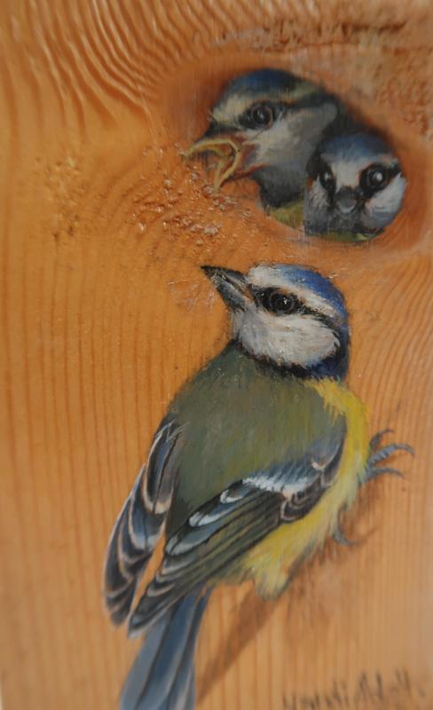 Blue tits painted on wood.