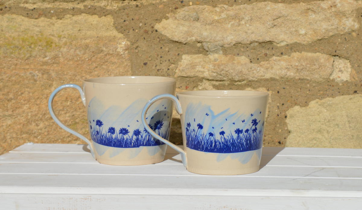 A pair of stoneware mugs with blue underglaze and meadow flower decoration £15 each