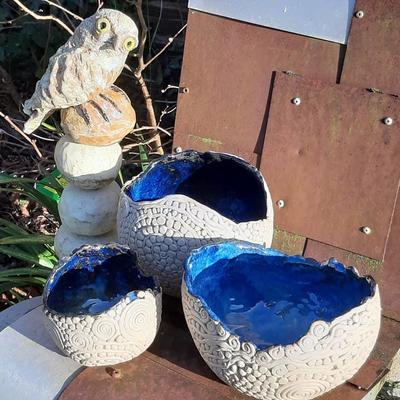 Stoneware life-size little owl on ceramic stacking stones & hand-textured blue-glazed coiled  bowls.
