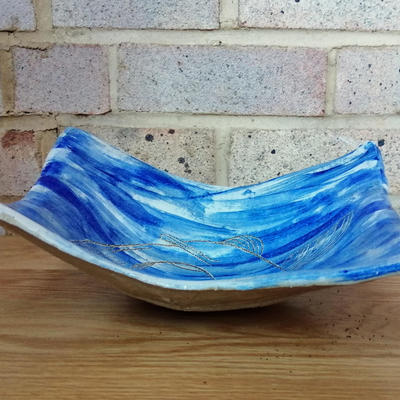 Blue and white ceramic bowl with sgraffito fish - side view