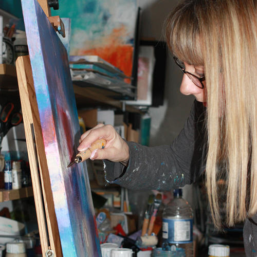 Photo of artist working on a painting on an easel