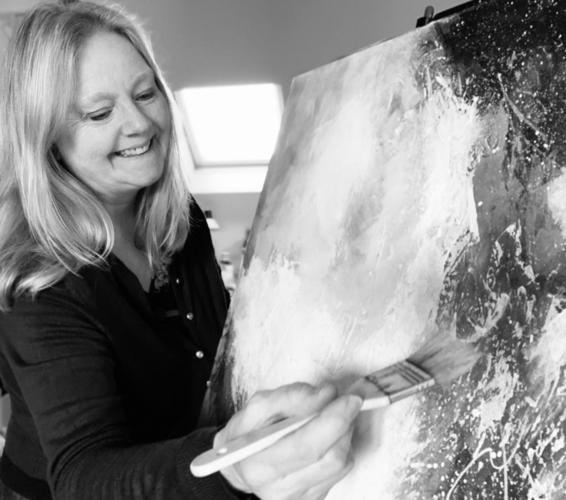 Julia Ogborne working on a canvas in the studio.