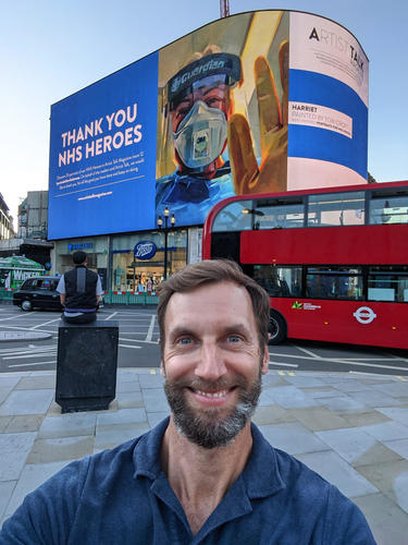 Tom Croft with his portrait of NHS Hero Harriet Durkin on the Piccadily Circus big screen